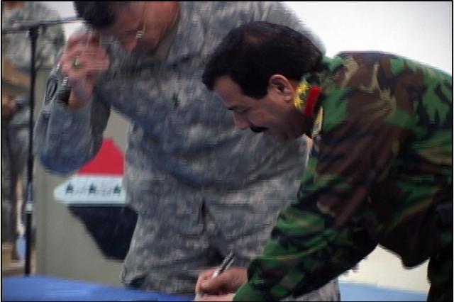 Brig. Gen. Khadir signs the contract after Maj. Gen.  Caslen.