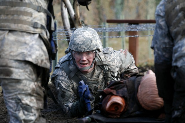 Spc. Cody Glasser pulls a dummy underneath barbed wire at the MSTC, Feb. 25.