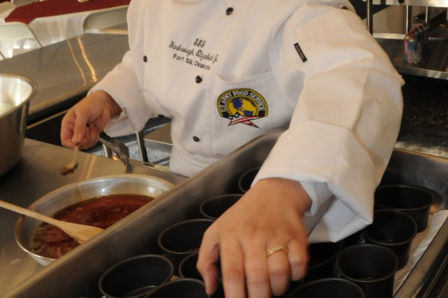 """Fort Sill's Staff Sgt. Elizabeth Yarbrough prepares caramel during the first few hours of the field competition held March 5. The field competition was of several cooking events that took place during the 34th Army Culinary Arts Competition held at Fort Lee, Va.,  Feb. 28-March 13. (Photo by T. Anthony Bell). """""""