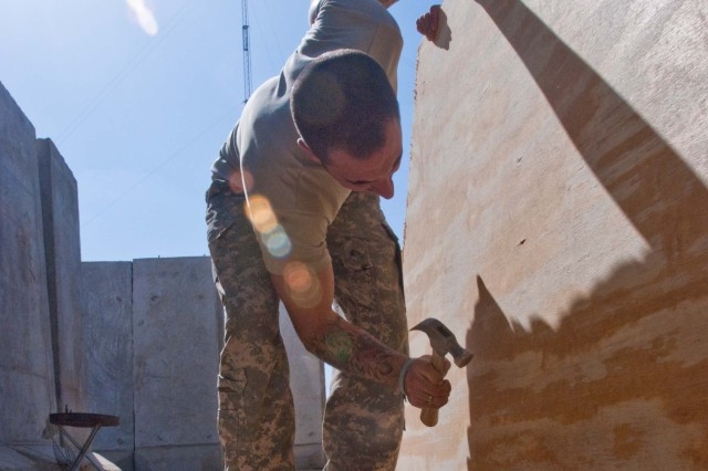 Sgt. David Hite, a member of the Black Dragon personal security detachment from Warrenton, Missouri, hammers a nail into a plywood wall while Sgt. Ader Villalta, another member of the security force from Los Angeles, braces the board for him. The Soldiers of the 5th Battalion, 82nd Field Artillery Regiment, 4th Brigade Combat Team, 1st Cavalry Division, are building up their housing areas on Forward Operating Base Hunter.