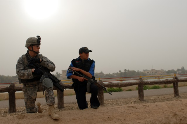BAGHDAD - Spc. Zachery Hughes, a team leader assigned to Troop B, 5th Squadron, 73rd Cavalry Regiment, 3rd Brigade Combat Team, 82nd Airborne Division, is mirrored by Ali Falaha, an Iraqi policeman, while kneeling in Abu Nawas Park on the banks of the Tigris River Feb. 27 in Baghdad.