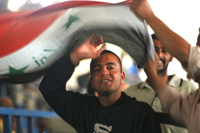 BAGHDAD - Iraqi students dance under an Iraqi flag before a graduation from a heavy equipment operator's course funded by the Coalition force March 5 at the Adl Sports Center in Kadamiyah.