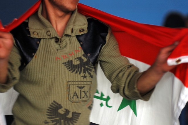 BAGHDAD -  An Iraqi student dances with an Iraqi flag before a graduation from a heavy equipment operator's course funded by the Coalition force March 5 at the Adl Sports Center in Kadamiyah. The students graduated from a three month long course.