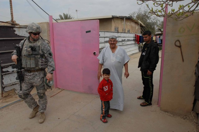 KEM, Iraq - Sgt. Norman Thomas of Philadelphia, a Soldier with the 1st Battalion, 111th Infantry Regiment, 56th Stryker Brigade Combat Team, 28th Infantry Division, bids farewell to an Iraqi family after a cordon and search in Kem village March 3.