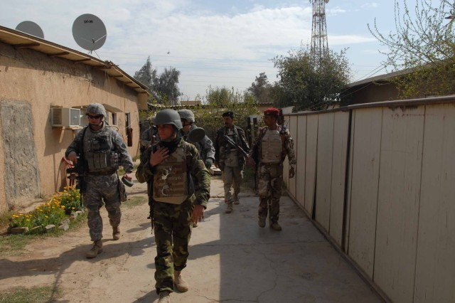 KEM, Iraq — Iraqi Army Soldiers work with Soldiers of the 856th Engineer Company and 1st Battalion, 111th Infantry Regiment (both are units of the 56th Stryker Brigade Combat Team, 28th Infantry Division) to conduct a cordon and search operation in Kem village March 3.