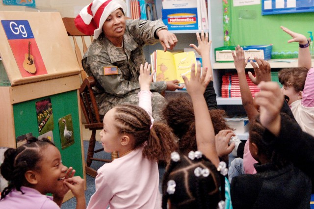 "Sgt. Maj. Khadijah Sellers of the U.S. Army TRADOC G-1/4 office at Fort Monroe, Va., shares the Dr. Seuss ""Foot Book"" with kindergarten students at John Tyler Elementary School in the City of Hampton during a Read Across America event on March 6. Nine Fort Monroe Soldiers and two DA Civilian employees volunteered for the program that's meant to encourage youngsters to read aloud to parents and other kids."