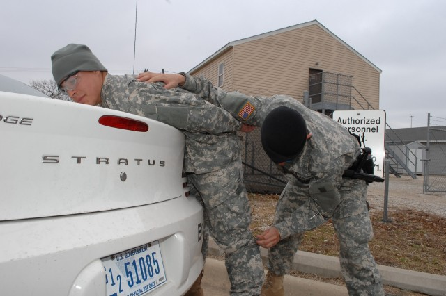 CUTLINE: Pfc. Josh Villa searches the pockets of Pfc. Chris Ortega, both Company E, 795th Military Police Battalion, during law and order training at Stem Village, Friday. The training teaches MP road duty requirements.