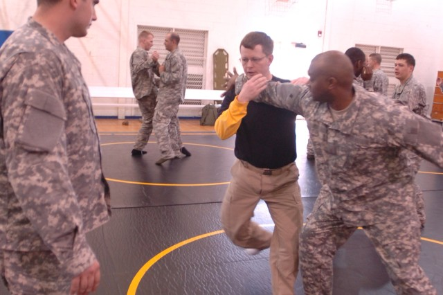 Brad Fowler, combatives instructor, battles with Sgt. Maj. Marcus Campbell, 3/7 Cav., 2nd BCT, during the three-day combatives course, Feb. 24 at Caro Gym.