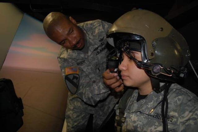 """Chief Warrant 3 Officer Joe Goode (left), an AH-64D Apache attack helicopter instructor pilot for the 1st Attack Reconnaissance Battalion, 227th Aviation Regiment, 1st Air Cavalry Brigade, 1st Cavalry Division, adjusts the Helmet Mounted Display for Lus Saucedo (right) a student from University High School's Army JROTC program in Waco, Texas. She was then given a target at which she fired rockets, missiles and the chain gun in the Apache flight simulator at Fort Hood, Texas, Feb. 26. Saucedo was one of many students who got to participate in a visit with """"First Attack"""" aviators."""