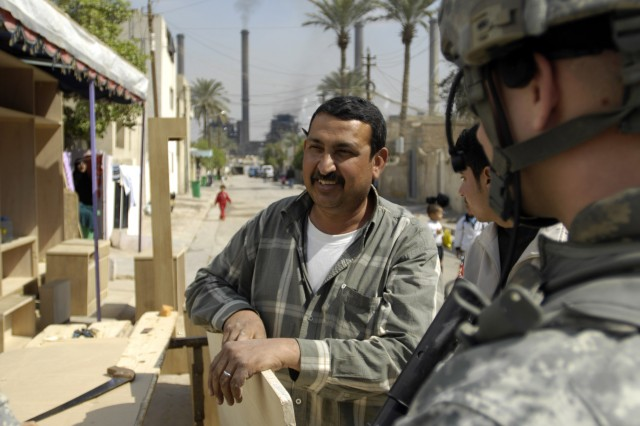 BAGHDAD - A shop owner discusses the current conditions of the Dora Marketplace with 1st Lt. Chris Timmerman, of Russia, Ohio, 1st Battalion, 505th Parachute Infantry Regiment, 3rd Brigade Combat Team, 82nd Airborne Division, during a patrol March 4.