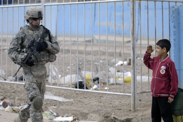 BAGHDAD - A young Iraqi boy stands and salutes Spc. Todd Bair of the1st Battalion, 505th Parachute Infantry Regiment, 3rd Brigade Combat Team, 82nd Airborne Division, during a combined patrol in the Dora Market area, Baghdad March 3.