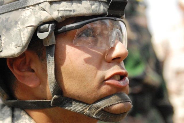 Pfc. Jacob Hester of San Jose, Calif., uses an interpreter to explain the field 'slump' test for concrete to Soldiers from the 6th Iraqi Army Engineer Regiment, March 4. Hester has only been in the Army for two years, but his knowledge is put to good use on a project site pouring concrete at Al Muthana Airfield, Baghdad. Hester is a member of the 46th Engineer Battalion, 225th Engineer Brigade, 1st Cavalry Division, Multi-National Division - Baghdad.