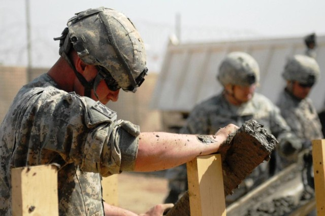 Lebanon, Miss. native Sgt. Daniel Bettes, an engineer from the 225th Engineer Brigade, knows only one way to demonstrate leveling concrete techniques to the 6th Iraqi Army Engineer Regiment, by jumping right in the mix March 4, at Al Muthana Airfield.