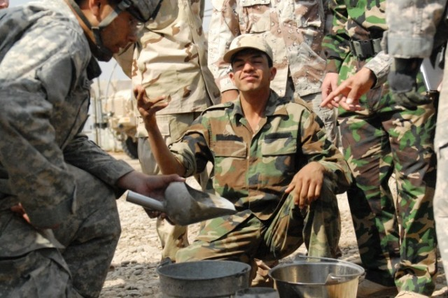 Pfc. Jacob Hester (left), of San Jose, Calif., an engineer with the 225th Engineer Brigade, demonstrates the field 'slump' test for concrete to engineers from the 6th Iraqi Army Engineer Regiment, March 4, at Al Muthana Airfield, Baghdad. Hester explained if the cement-to-water ratio is correct, the concrete should only fall one to three inches when removed from the cylinder.