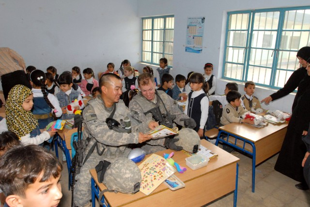 BAGHDAD - Staff Sgt. Raymond Wong (left) a New York City native, and Sgt. Peter Farley, a Middlesboro, Mass. native, both with the  340th Military Police Company, Task Force 91 MP, 8th MP Brigade, Multi-National Division - Baghdad, take a break at a student's desk at the Al Tadhia Primary School, in New Baghdad, Feb. 25.  Soldiers of the 340th and local Iraqi Police delivered basic school supplies, donated from state side, to more than 500 student of the school.  Farley, a fourth grade teacher in Brockton, Mass., was instrumental in organizing the mission he named Operation Iraq Tomorrow, and its success.