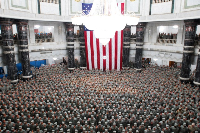 In this file photo, 1,215 U.S. servicemembers from all over Iraq re-enlist during a ceremony in the Al Faw Palace rotunda at Camp Victrory in Baghdad, July 4, 2008. New pressures from the economy, which have helped the Army meet retention goals, may cause some reenlistment bonuses to decrease or all together vanish.