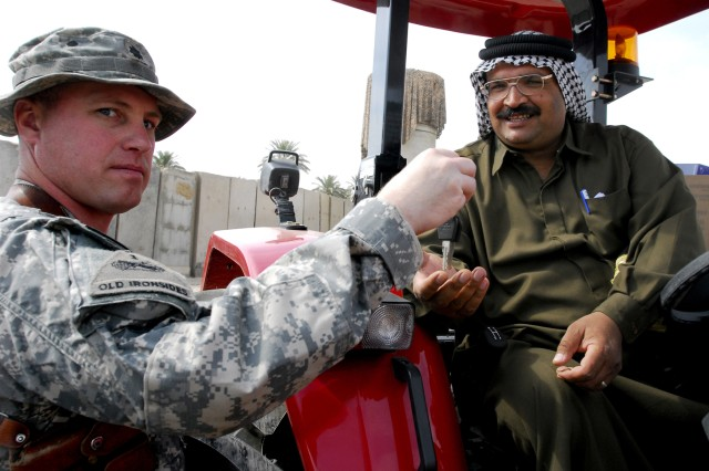 Lt. Col.  Michael Mammay, commander of Task Force 4th Battalion, 27th Field Artillery, hands keys to a new ArmaTrac 602 tractor to Sheik Musa, a local leader in Iraq's Lutifiyah Nahia region, during a ceremony at Combat Outpost Meade March 5. The battalion donated 14 of the new machines for the use of farmers in the area.
