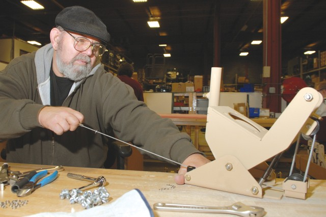 Jerry Pursel, sheet metal mechanic helper, tests the pull-down kit assembly attached to a CREW antenna system flex-mount device.  The pull-down assembly allows the antenna to tilt down prior to coming into contact with a hard object such as an overpass, bridge or low-hanging wires.  Pursel works in the Assembly Branch.