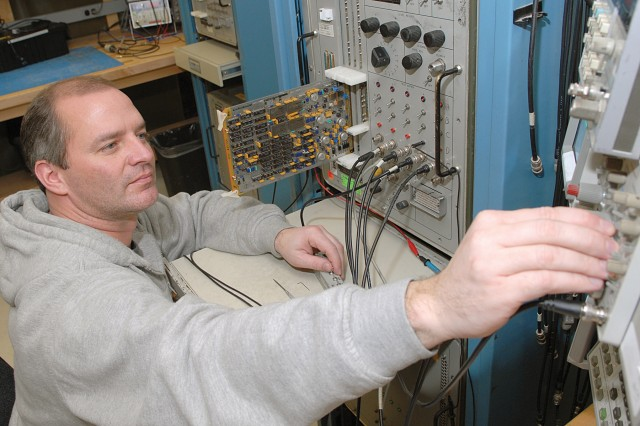 Thomas Kleeman, electronics mechanic, aligns and tests a circuit card used in the AN/TRC-170 system's receive modem.