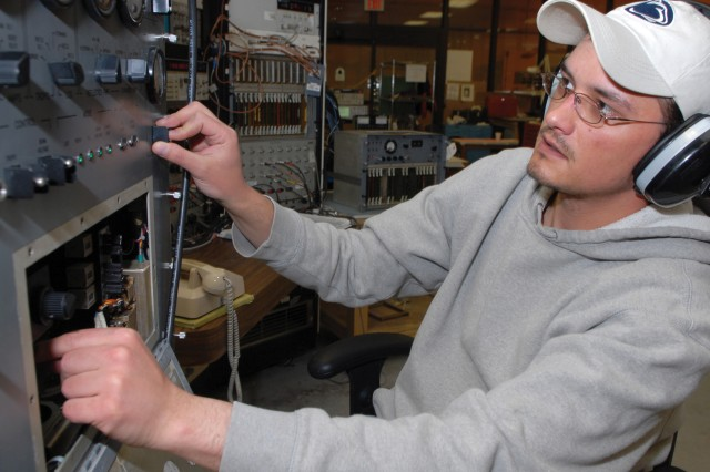 William Chuma, electronics mechanic, performs electrical testing and alignment of the AN/TRC-170 system's transit modem.
