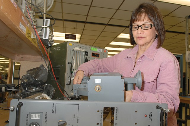 Catherine Marino, electronics mechanic, reassembles a converter after mechanical overhaul.