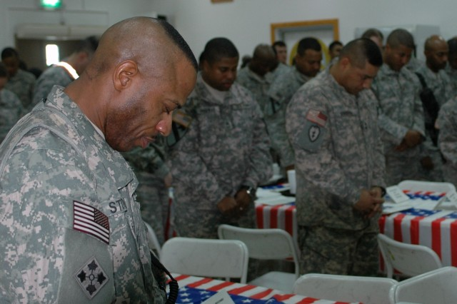 Attendees of the black history celebration held at the FOB Marez dining facility in Mosul, Iraq on Feb 18, join in prayer during the invocation.