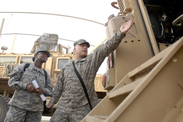 """Staff Sgt. Randy Maurer (right), a medic serving with Company C, 299th Brigade Support """"Lifeline"""" Battalion, shows the inside of a Heavy Armored Ground Ambulance to Command Sgt. Maj. Althea Dixon, senior enlisted advisor to the Army Surgeon General, at the Riva Ridge Troop Medical Clinic on Camp Liberty, Iraq, March 5. (U.S. Army photo by"""