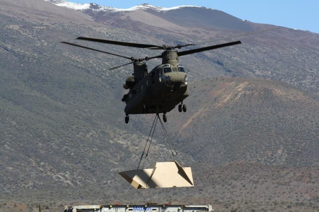 """A 25th CAB CH-47D Chinook helicopter lifts one of 28 """"EOD-T"""" targets for placement at one of several ranges at Pohakuloa Training Area, on the big island of Hawaii. The EOD-T targets are designed to simulate typical threat and non-threat military vehicles for live-fire training."""