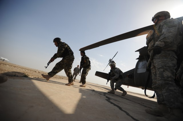 Iraqi policemen, from the Dhi Qar Province exit a UH-60 Blackhawk helicopter and prepare to pull security during an air assault training event with Soldiers of the 2nd Battalion, 12 Cavalry Regiment, 4th Brigade Combat Team, 1st Cavalry Regiment, at Camp Cedar, Iraq, March 2.