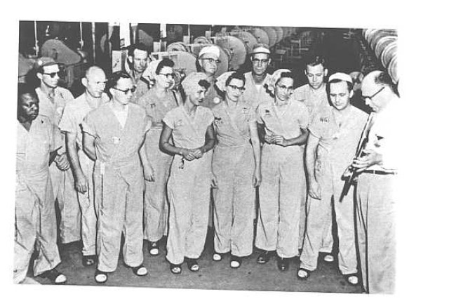 "A group (commonly referred to as a ""unit"") of production workers at the Twin Cities Ordnance Plant. Note that there are several women and one African-American in this group. Also note the uniforms and special shoes issued to the workers. The shoes are designed to not generate static electricity (TCAAP Public Information Office)."