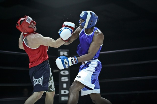 1st Lt. Donald Hamilton (red) of Sacramento, Calif., fighting for 1st Brigade, 1st Armored Division, Fort Bliss, Texas, reels from a solid blow delivered by Pfc. Joshua Hunter (blue) of New York City, fighting for III Corps, Fort Hood, Texas. The boxing was part of finals night for the III Armored Corps and Fort Hood first-ever Boxing Smoker held at Abrams Field House, Fort Hood, Texas, March 5.
