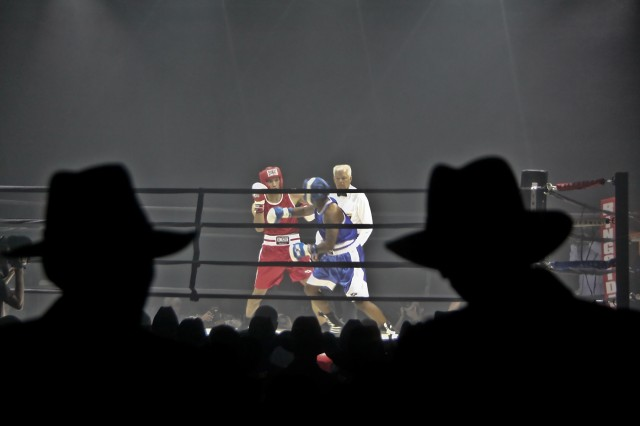 In front of an audience full of Stetsons, Spc. James Hollon (red) of New Braunfels, Texas, 36th Engineering Brigade, and Pfc. Marques Johnson (blue) of Cincinnati, 1st Medical Brigade, both of Fort Hood, Texas, trade blows during the welterweight final as part of the III Armored Corps and Fort Hood, first-ever Boxing Smoker, held at Abrams Field House on Fort Hood, Texas, March 5.