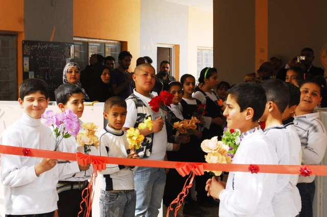 Students in Althaira await the ribbon cutting ceremony to celebrate the re-opening of their school March 8. The school was built in 1971 and has the largest student enrollment in Althaira, Mahmudiyah Qada. Local construction contractors remodeled and built an addition to the school to accommodate 485 students.