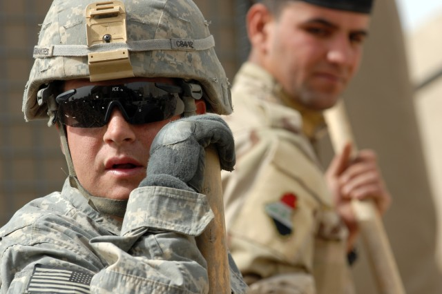 BAGHDAD - Tomah, Wisc. native, Spc. William Ruhling, a concrete and asphalt equipment operator assigned to Company B, 46th Engineer Battalion, 225th Eng. Brigade, works while practicing his Arabic with members of the 6th Iraqi Army Engineer Regiment March 8 at al-Muthana Airfield.