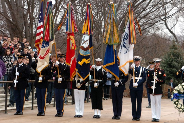 A joint armed forces color guard presents arms during a wreath ceremony in honor of Admiral Giampaolo Di Paola , the Chairman of the North Atlantic Treaty Organization Military Committee at the Tomb of the Unknown Soldier in Arlington National Cemetery.
