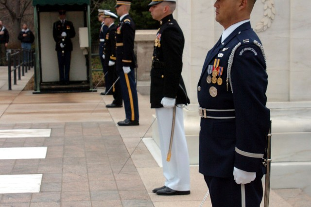 A joint force honor guard presents arms as Admiral Giampaolo Di Paola , the Chairman of the North Atlantic Treaty Organization Military Committee lays a wreath at the Tomb of the Unknown Soldier in Arlington National Cemetery.