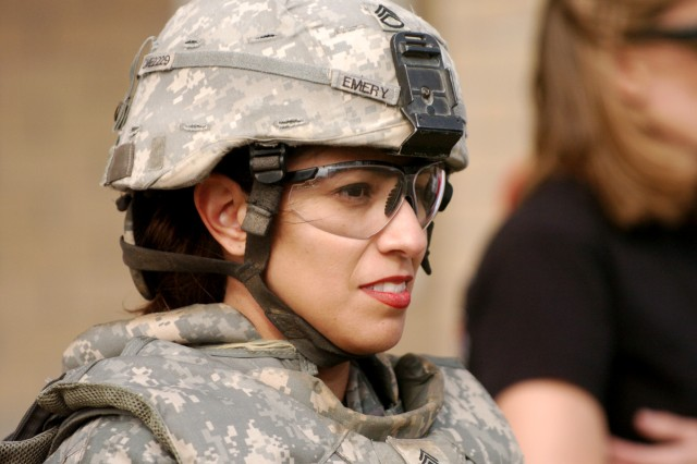 Janie Emery, of Killeen, Texas, wears all a Soldiers' protective gear as she listens to the grenade station's grader at the grenade toss station March 6, during 4th Brigade Combat Team, 1st Cavalry Division's, Spouses' Spur Ride at