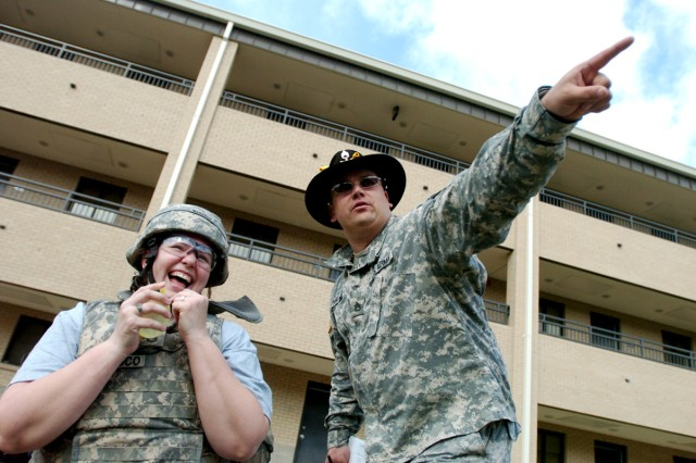 Meagan Khan, of Ocean, N.J., laughs as Staff Sgt. Wayne Bunnell, of Muskeon, Mich., instructs her to throw the water balloon grenade at a Soldier holding up a cardboard target at the grenade station March 6, during 4th Brigade Combat Team, 1st Cavalry Division's, Spouses' Spur Ride at Fort Hood, Texas.