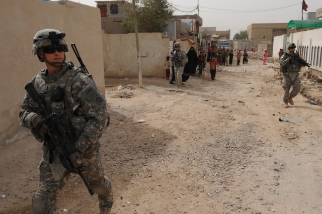 "SHAWRA WA UM JIDIR, Iraq - 1st Lt. Elliot Proctor (left), a platoon leader assigned to Company B, 2nd Battalion, 505th Parachute Infantry Regiment, move down the street to a nearby school in the city of Shawra Wa Um Jidir during ""Operation Dub Chabeer 2"" March 8 in the 9 Nissan district of eastern Baghdad.  Paratroopers assigned to Co. B, along with National Police officers assigned to the 2nd Bn., 8th NP Bde., 2nd NP Div., visited seven local schools and distributed supplies to hundreds of children in the poverty stricken district."