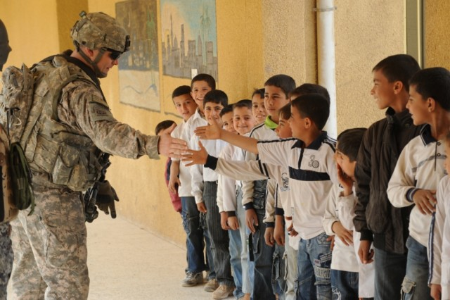 "SHAWRA WA UM JIDIR, Iraq - Sgt. 1st Class Eric Stein, a platoon sergeant assigned to Company B, 2nd Battalion, 505th Parachute Infantry Regiment, gives a high five to Iraqi schoolboys lined up to receive book bags from National Police officers assigned to the 2nd Bn., 8th NP Bde., 2nd NP Div., and paratroopers of Co. B., during ""Operation Dub Chabeer 2"" March 8 in the 9 Nissan district of eastern Baghdad. The combined operation distributed hundreds of school supplies to seven area schools in the poverty stricken district to enhance the children's education."
