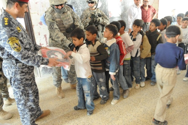 """SHAWRA WA UM JIDIR, Iraq - An National Police officer assigned to the 2nd Battalion, 8th NP Brigade, 2nd NP Division gives an Iraqi boy a book bag at a school in the city of Shawra Wa Um Jidir March 8 in the 9 Nissan district of eastern Baghdad.  NP officers and Paratroopers assigned to Company B, 2nd Battalion, 505th Parachute Infantry Regiment, visited several schools during """"Operation Dub Chabeer 2."""" The combined operation was a humanitarian mission to hand out hundreds of school supplies to students in seven different schools across the city."""