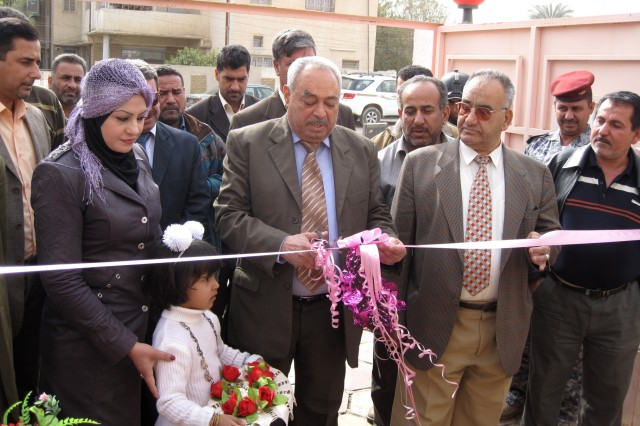 MUSTANSIRYA, Iraq - Mr. Faysal Jasim Mohammad, deputy district council chairman, cuts the ceremonial ribbon to officially reopen the renovated Al-Moutasam Kindergarten March 3 in the Rusafa district of eastern Baghdad. District leaders, school officers, Iraqi Security Forces and paratroopers assigned to 5th Squadron, 73rd Cavalry Regiment were in attendance to commemorate the school's renovation and reopening.