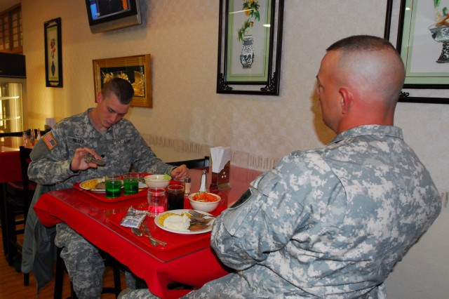 "Spc. Tyler Miller, left, and Sgt. 1st Class Ward Christman, 8th Theater Sustainment Command G-3, eat their ""breakfast"" before their night shift at the Camp Zama, Japan, dining facility.  The Soldiers deployed to Camp Zama as part of the 8th TSC forward command post for a two-week exercise."