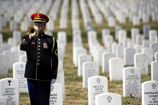 A lone U.S. Army bugler plays taps at the conclusion of the First Annual Remembrance Ceremony in Dedication to Fallen Military Medical Personnel at Arlington National Cemetery, March 11, 2009.