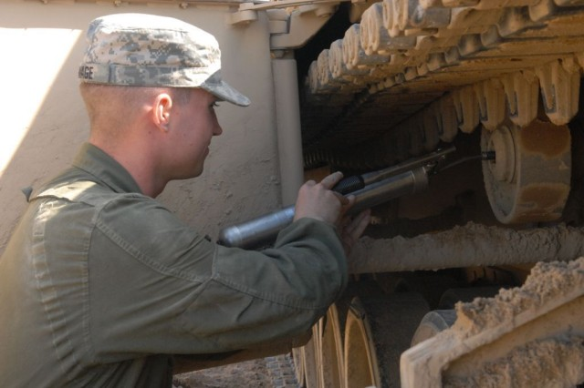 """Specialist Geoffrey Savage, Company C, 1st Battalion, 15th Infantry Regiment, 3rd Heavy Brigade Combat Team, 3rd Infantry Division, greases a wheel on the M1-A1SA Abrams tank he drives Feb 26 at Hastings Range.  Savage and his fellow crew members earned """"top tank"""" honors in the battalion during tank qualification Feb. 22 - 28 at Fort Benning, Ga."""