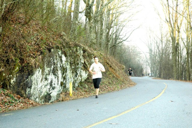 """FORT MCPHERSON, Ga. -- Movin' right along! Staff Sgt. Ivy Perkins, a paralegal NCO for U.S. Army Central, rounds a corner running up the mountain. Perkins, known for spending her lunch time in the gym, was taking part in the USAG hosted """"Fun Run"""" commemorating the 2009 - Year of the Noncommissioned Officer Mar. 11. This month's theme for the year long event is """"Focus on Fitness."""""""