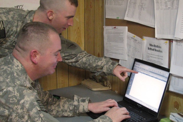 Spc. Jeffrey Powers (sitting) and Spc. Mark Lefevres, medics with the 115th CSH, electronically record patient data via MC4 at Camp Bucca, Iraq.