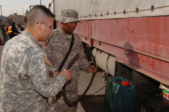 Staff Sgt. Leroy Cain, a 609th Movement Control Team transportation managing coordinator and Wilmington, N.C., native, and an interpreter check a piece of hose found in an underneath compartment of a driver's trailer at Habur Gate, Iraq. Hoses are commonly taken during inspections as they could be used to steal fuel. (U.S. Army photos by Spc. Michael Behlin)