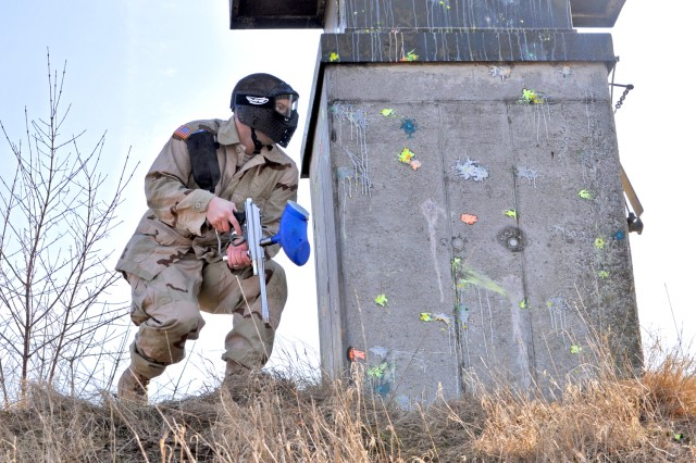 A participant in Wiesbaden's Warrior Adventure Quest takes cover before attacking his opponents during a paintball game at the BLASA range in Wiesbaden.