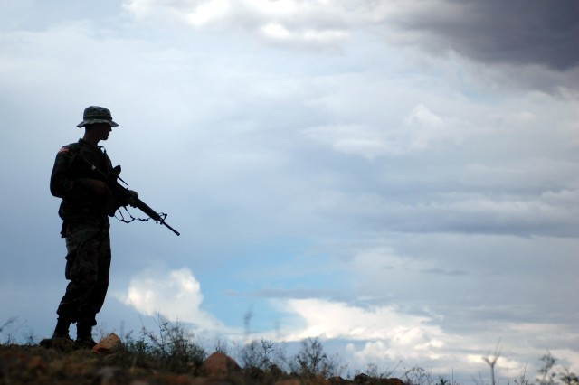 In this file photo, a National Guard Soldier from the 29th Brigade Combat Team, assisting the U.S. Border Patrol, stands watch on a ridge above Nogales, Ariz., at the Mexico border, Aug. 3, 2006.